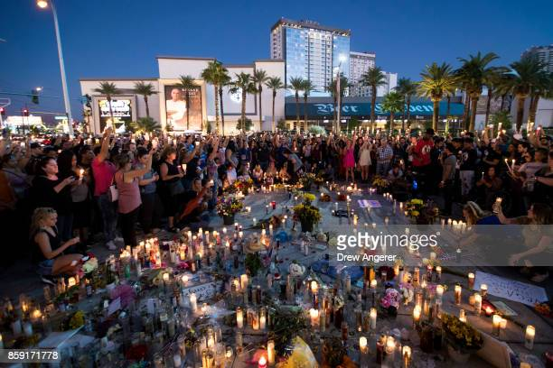 Mourners hold their candles in the air during a moment of silence during a vigil to mark one week since the mass shooting at the Route 91 Harvest...