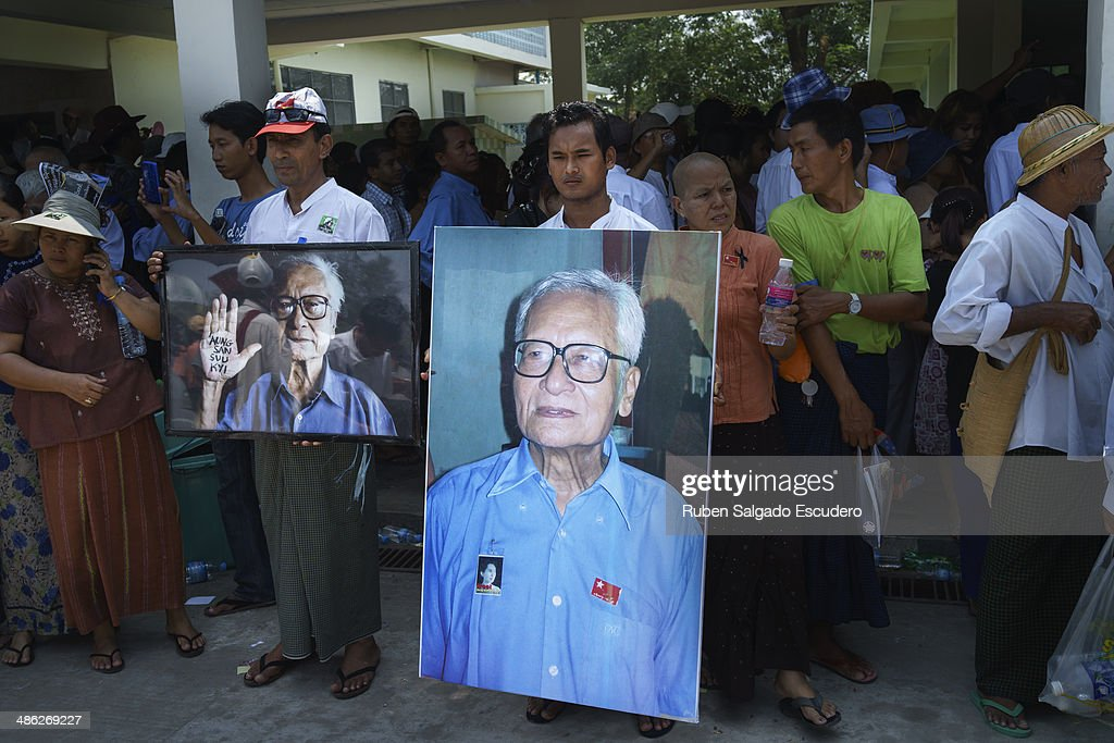 Mourners hold up photos of Win Tin to pay respect during Win Tin's memorial service in Yay Way cemetery on April 23, 2014 in Yangon, Burma. The Burmese journalist who helped Aung San Suu Kyi launch a pro-democracy movement against the junta military regime, died April 21 in Rangoon.