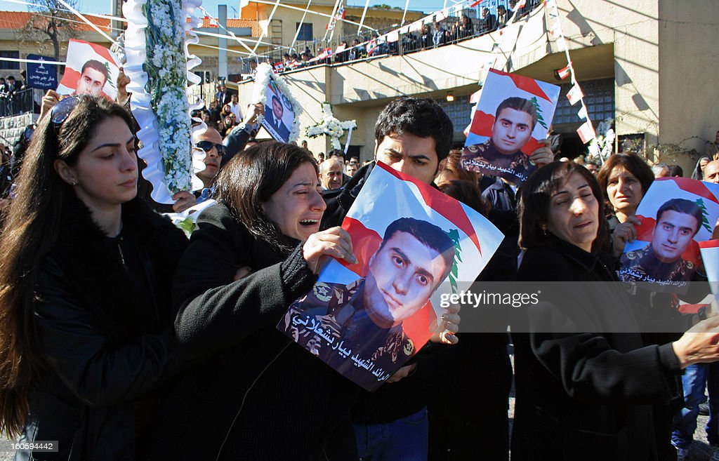 Mourners, holding pictures of Lebanese army captain Pierre Bashalana, one of the two soldiers who were killed in a clash with unidentified gunmen in Arsal, a village near the border with Syria, attend his funeral procession in the city of Mraijat, on the outskirts of Beirut, on February 3, 2013. Bashalana was killed alongside sergeant Ibrahim Zahrman while several others were wounded in the clash with an unspecified number of gunmen, who also sustained casualties on February 1. AFP PHOTO / STR
