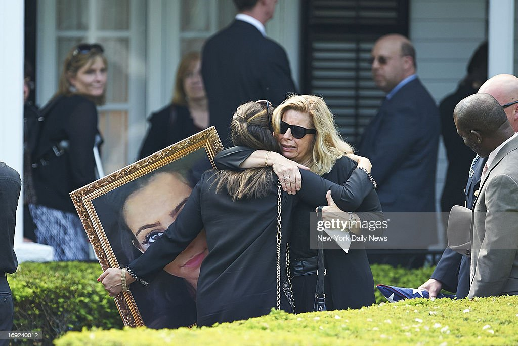 Mourners hug as they hold a photo of shooting victim Andrea Rebello, 21, at her wake at the Coffey Funeral Home on in Tarrytown, N.Y. Rebello, of Tarrytown, N.Y., was shot to death by a Nassau County police officer who responded to a robbery of Rebello's off-campus home in Uniondale, L.I. An armed intruder with a long rap sheet, Dalton Smith, was holding Rebello hostage and using her as a human shield when the officer, a veteran cop who had previously served with the NYPD fired eight shots.