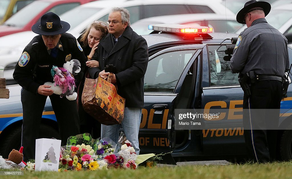 Mourners including a Newtown Police officers gather at a makeshift memorial outside St. Rose of Lima Roman Catholic Church during the first day of Sunday services following the mass shooting at Sandy Hook Elementary School on December 16, 2012 in Newtown, Connecticut. Twenty six people were shot dead, including twenty children, after a gunman identified as Adam Lanza in news reports opened fire in the school. Lanza also reportedly had committed suicide at the scene.
