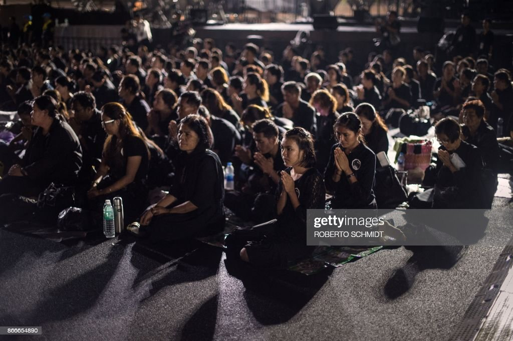 TOPSHOT - Mourners kneel down and pray while waiting in front of the cremation grounds where the body of late Thai King Bhumibol Adulyadej's body was taken to be cremated in Bangkok on October 26, 2017. A sea of black-clad mourners massed across Bangkok's historic heart early on October 26 as funeral rituals began for King Bhumibol Adulyadej, a revered monarch whose passing after a seven-decade reign has left Thailand bereft of its only unifying figure. /