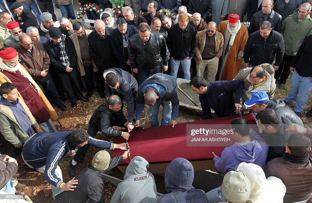Mourners lay to rest the body of High Priest of the Samaritan community Harun Abu Al-Hasan, 84, during his funeral in Mount Gerizim near the West Bank city of Nablus on April 19, 2013.PHOTO