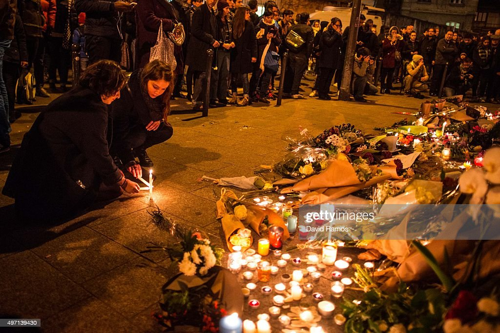 Mourners leave candles in front of the Le Carillon restaurant on November 14 2015 in Paris France At least 120 people have been killed and over 200...