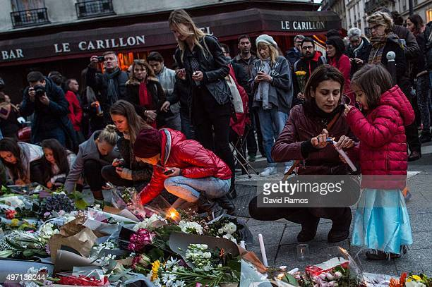 Mourners leave candles in front of the Petit Cambodge restaurant with the Le Carillon restaurant on the background on November 14 2015 in Paris...