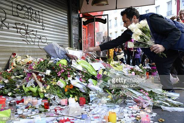 Mourners leave flowers and candles at a memorial site on November 15 outside of the Le Belle Equipe in the 11th district of Paris for victims of the...