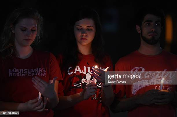 Mourners light candles during a candlelight vigil held on the campus of Louisiana Lafayette on July 24 2015 in Lafayette Louisiana Two people were...