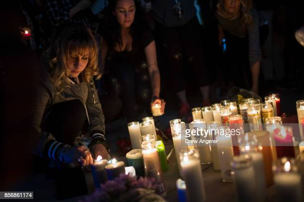 Mourners light candles during a vigil at the corner of Sahara Avenue and Las Vegas Boulevard for the victims of Sunday night's mass shooting October...