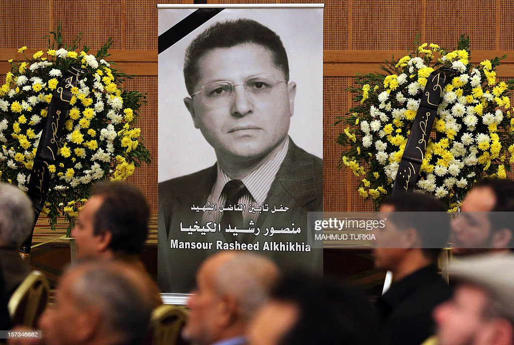 Mourners listen as the President of the General National Congress of Libya, Mohammed Megaryef (unseen), speaks during a memorial service for leading Libyan dissident, Mansour Rashid al-Kikhia (portrait), in Tripoli on December 2, 2012. Kikhia, who disappeared 19 years ago under the Kadhafi regime, is to be buried on December 3, weeks after his body was found in an intelligence services morgue, his brother said.