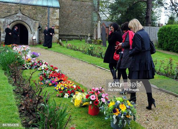 Mourners look at floral tributes as they attend the funeral of Claire Squires at St Andrew's Church in North Kilworth Leicestershire after she...