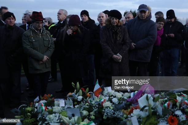 Mourners look at the grave after Martin McGuinness' Funeral at the Derry City Cemetery on March 23 2017 in Londonderry Northern Ireland The funeral...