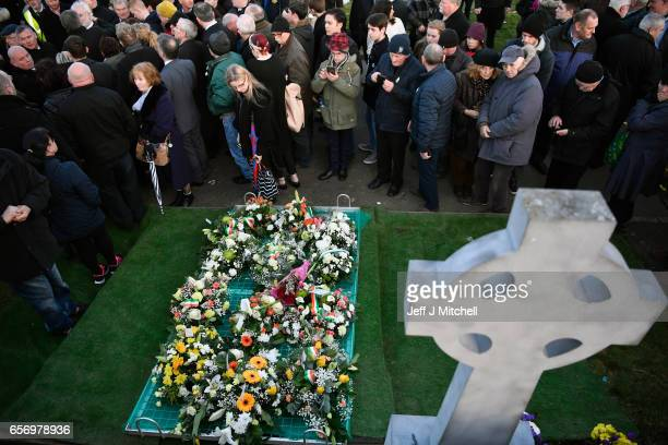 Mourners look on during Martin McGuinness' Funeral at the Derry City Cemetery on March 23 2017 in Londonderry Northern Ireland The funeral is held...