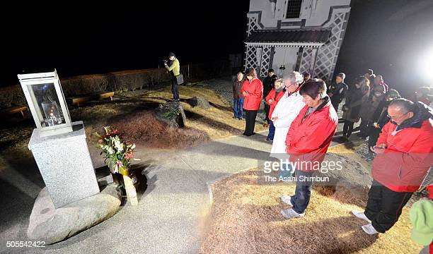 Mourners observe a minute of silience as Japan marks the 21st anniversary of the Great Hanshin Earthquake on January 17 2016 in Ishinomaki Iwate...