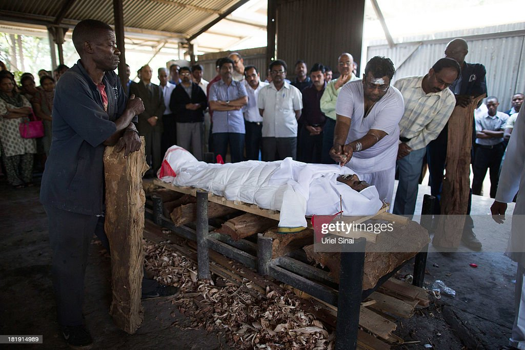 Mourners observe the body of Sridhar Natarajan, who was killed at the at the Westgate Mall attack during his funeral ceremony on September 26, 2013 in Nairobi, Kenya. The country is observing three days of national mourning as security forces begin the task of clearing and securing the Westgate shopping mall following a four-day siege by militants.