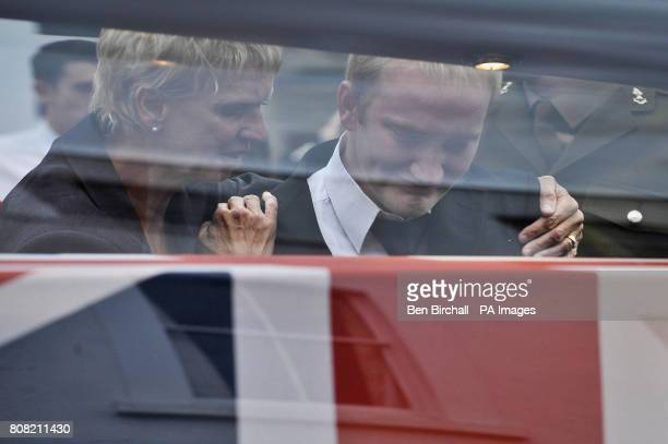 Mourners pause by the glass on the hearse and look at the Union Flag draped coffins containing the bodies of Sapper Darren Foster of 21 Engineer...
