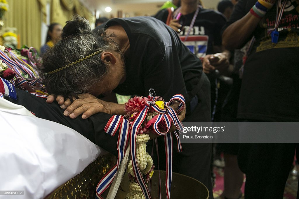 Mourners pay their respects over the body of Sutin Tharatin, a core anti-government leader who was killed by gunmen yesterday, on January 27, 2014 in Bangkok, Thailand. Nine others were also injured during election related violence as protesters blocked polling stations as advanced voting took place in the capitol city. Bangkok Shutdown has been in effect for two weeks as the anti-government protesters continue to block major intersections. The Thai government imposed a 60-day state of emergency in Bangkok and the surrounding provinces in an attempt to cope with the on-going political turmoil but so far this decree has had no effect on the mass protests.