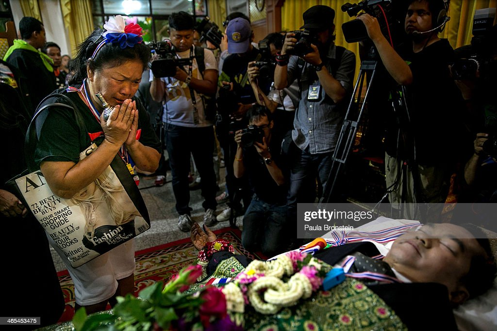Mourners pay their respects over the body of Sutin Tharatin, a core anti-government leader who was killed by gunmen yesterday in Bangkok on January 27, 2014 in Bangkok, Thailand. Nine others were also injured during election related violence as protesters blocked polling stations as advanced voting took place in the capital city. Bangkok Shutdown has been in effect for two weeks as the anti-government protesters continue to block major intersections. The Thai government imposed a 60-day state of emergency in Bangkok and the surrounding provinces in an attempt to cope with the on-going political turmoil but so far this decree has had no effect on the mass protests.