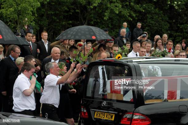 Mourners pay their respects to Captain Stephen Healey from the 1st Battalion The Royal Welsh Guards as his body passes the Memorial Garden in...