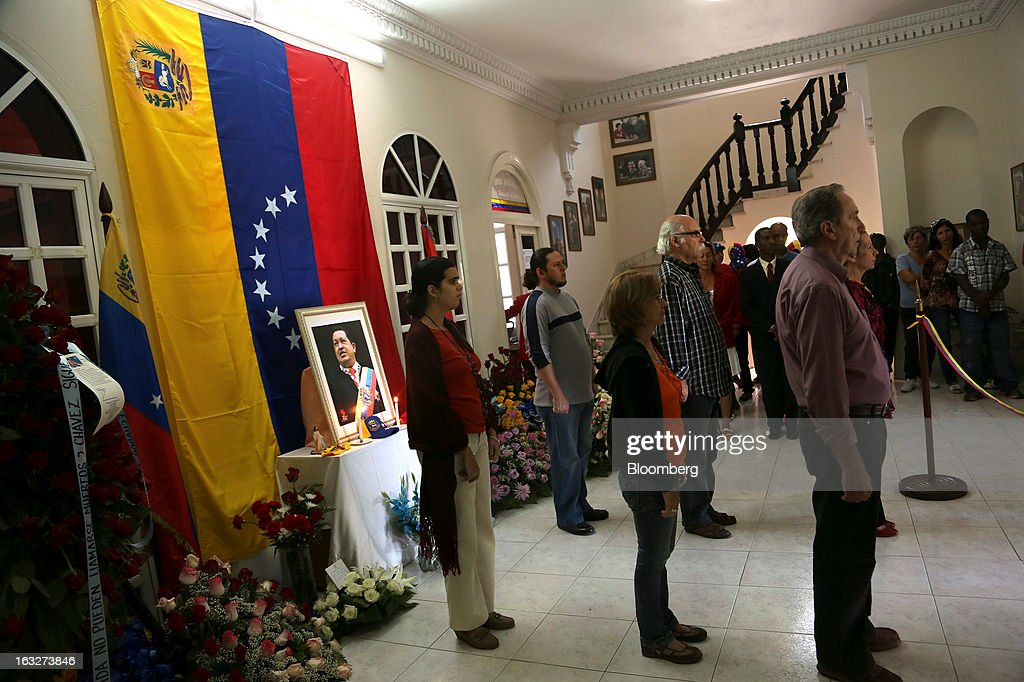 Mourners pay their respects to deceased Venezuelan President Hugo Chavez during a ceremony at Venezuela's embassy in Havana, Cuba, on Wednesday, March 6, 2013. Cuba's government praised Chavez following his death yesterday for uniting the people of Latin America and pledged loyalty to the continuation of his Bolivarian Revolution, according to the statement in the state-run Granma website. Photographer: Noah Friedman-Rudovsky/Bloomberg via Getty Images