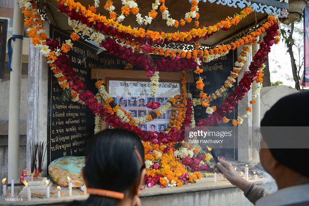 Mourners perform rituals at a memorial outside the Swaminarayan Vidhyalaya on the twelfth anniversary of the Gujarat earthquake in Ahmedabad on January 26, 2013t. Some 32 students of this school died in the quake that killed over 19,000 people. AFP PHOTO / Sam PANTHAKY