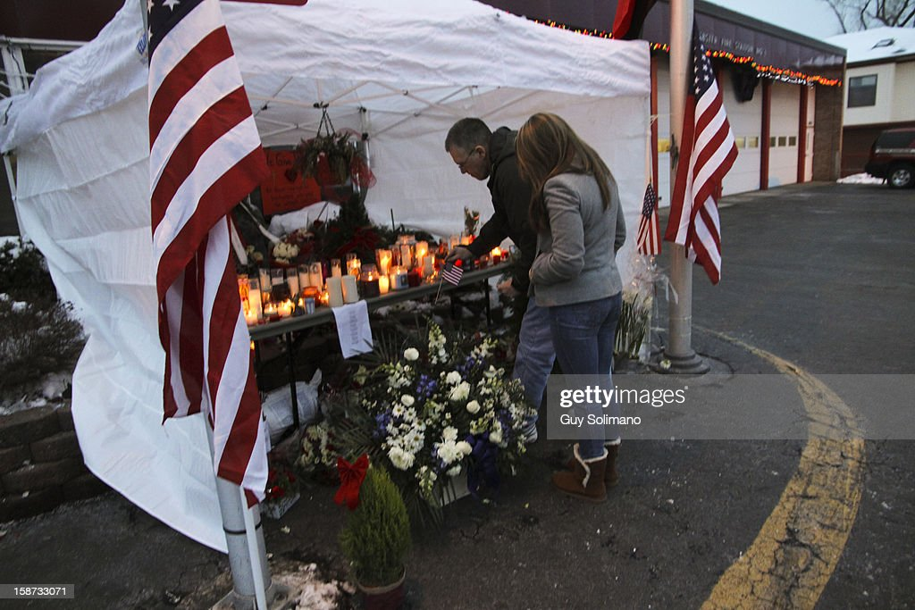 Mourners place an American flag at a a makeshift memorial at the West Webster Fire Station on Wednesday, December 26, 2012 in Webster, New York. Law enforcement officials have not publicly identified which gun or guns were used to shoot the four firefighters, two of them fatally, or in what authorities have described as a brief standoff between William Spengler Jr., and a Webster police officer on Christmas eve.