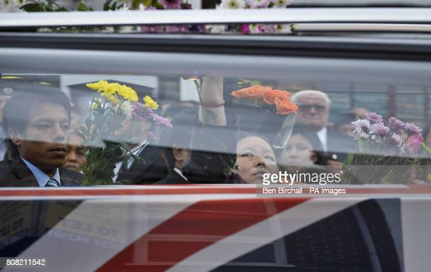 Mourners place flowers on top of a hearse as the Union Flag draped coffins containing the bodies of Sapper Darren Foster of 21 Engineer Regiment and...