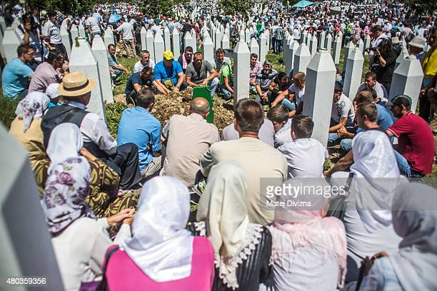 Mourners pray at the fresh grave of one of 136 newlyidentified victims of the 1995 Srebrenica massacre during a mass funeral attended by tens of...