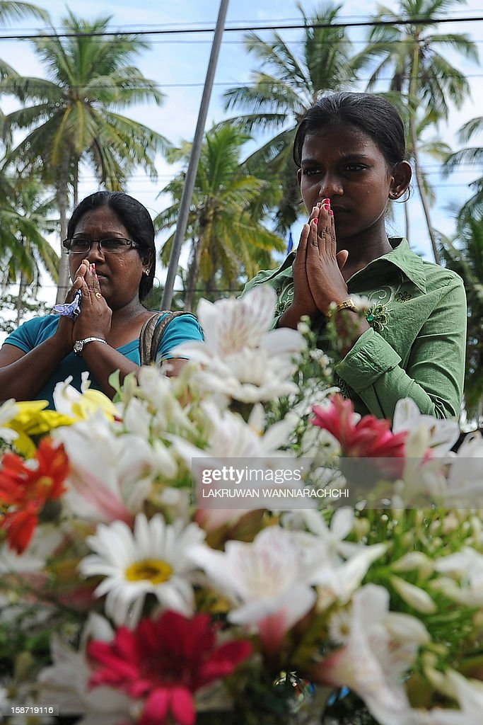 Mourners pray during a ceremony held to commemorate victims of the December 2004 tsunami at Peraliya village in southern Sri Lanka on December 26, 2012, on the eighth anniversary of the disaster. Some 31,000 people on the island died during the 2004 Asian tsunami and one million were initially left homeless.