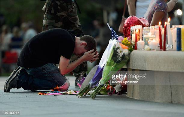 Mourners pray in front of a makeshift memorial after a prayer vigil at the Aurora Municipal Center for the victims of the mass shooting at Century 16...
