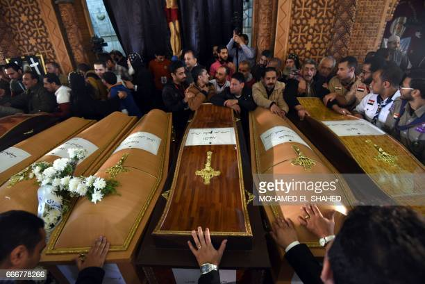 Mourners pray next to coffins of the victims of the blast at the Coptic Christian Saint Mark's church in Alexandria the previous day during a funeral...