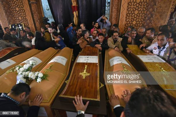 Mourners pray next to coffins of victims of the blast at the Coptic Christian Saint Mark's church in Alexandria the previous day during a funeral...