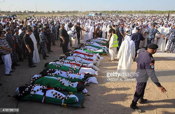 Mourners pray over the bodies of the victims of the AlImam AlSadeq mosque bombing during a mass funeral at Jaafari cemetery in Kuwait City on June 27...