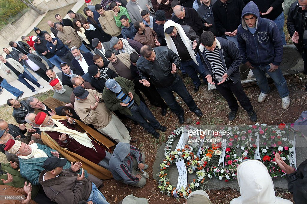Mourners pray over the body of High Priest of the Samaritan community Harun Abu Al-Hasan, 84, during his funeral in Mount Gerizim near the West Bank city of Nablus on April 19, 2013.PHOTO