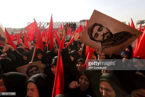 Mourners raise portraits of Mohsen Hojaji a young member of Iran's elite revolutionary guards Corps who was beheaded in Syria by Islamic State group...