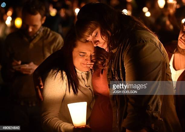 Mourners react during a vigil in Roseburg Oregon on October 1 for ten people killed and seven others wounded in a shooting at a community college in...