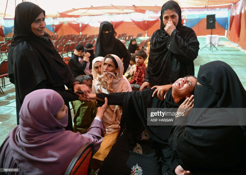 Mourners react during the funeral of garment factory fire victims, their bodies released by authorities after months of forensics investigations following their deaths in the incident September last year, during a funeral in Karachi on February 24, 2013. Pakistani police have moved to drop murder charges against the owners of a garment factory where 289 workers were killed in a fire in September 2012, the mens' lawyer said February 11. AFP PHOTO/Asif HASSAN