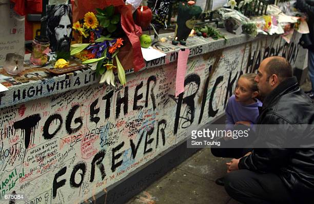 Mourners read messages and cards attached to the wall of Abbey Road Recording Studios December 2 2001 after the death of musician George Harrison An...