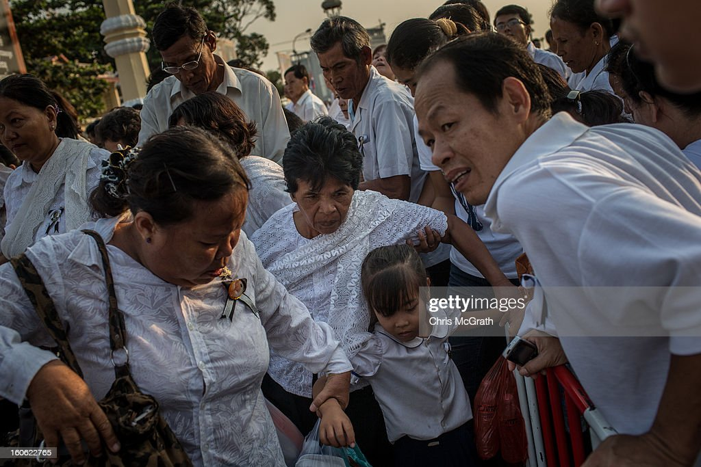 Mourners rush and push through barricades to get to the front of the line to enter the cremation site to pay their final respects to former King Norodom Sihanouk ahead of tonight's cremation on February 4, 2013 in Phnom Penh, Cambodia. The former kings coffin was transported to the cremation site after being paraded through the capital in a lavish funeral procession. The cremation will take place on Monday evening the funeral pyre will be lit by his wife and son King Norodom Sihamoni.