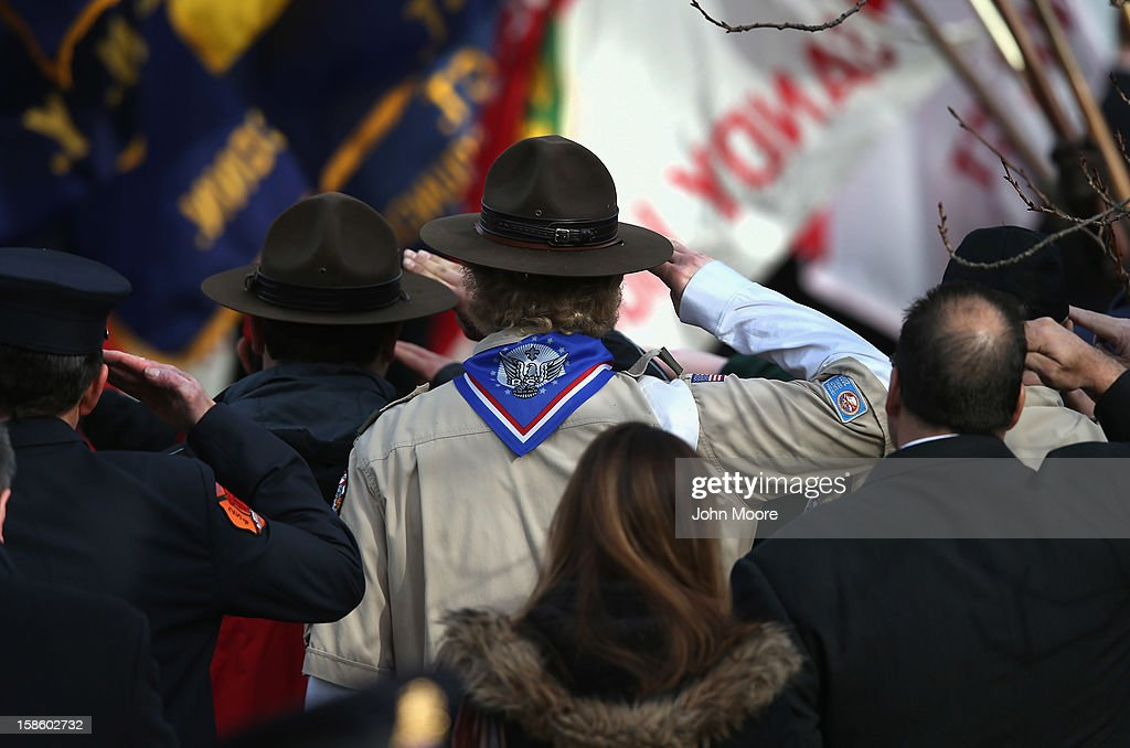 Mourners salute as the funeral procession for Benjamin Wheeler, 6, departs the Trinity Episcopal Church on December 20, 2012 in Newtown, Connecticut. Benjamin, a member of Tiger Scout Den 6, was killed when 20 children and six adults were massacred at Sandy Hook Elementary School last Friday. Six services were held for students and teachers in the Newtown area Thursday.