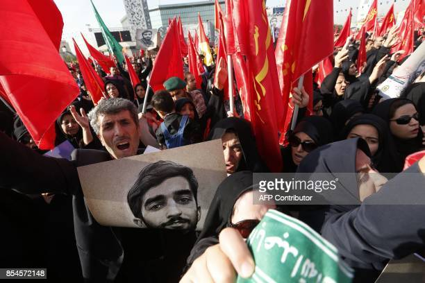 Mourners shoud slogans as they raise portraits of Mohsen Hojaji a young member of Iran's elite revolutionary guards Corps who was beheaded in Syria...