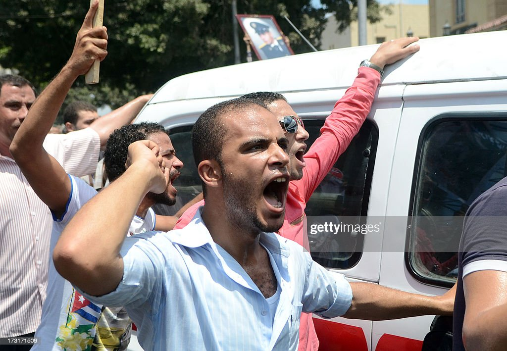 Mourners shout as they walk along side a vehicle carrying the coffin of a police officer killed in clashes between protestors and security forces during his funral in the northern coastal city of Alexandria on July 9, 2013. Egypt's interim leader vowed fresh elections by early next year as Islamists prepared to rally after dozens of ousted president Mohamed Morsi's loyalists died in clashes at a Cairo military barracks the day before. The Muslim Brotherhood released the names of 42 people killed in the incident, as the interior ministry and military said two policemen and a soldier were also killed.