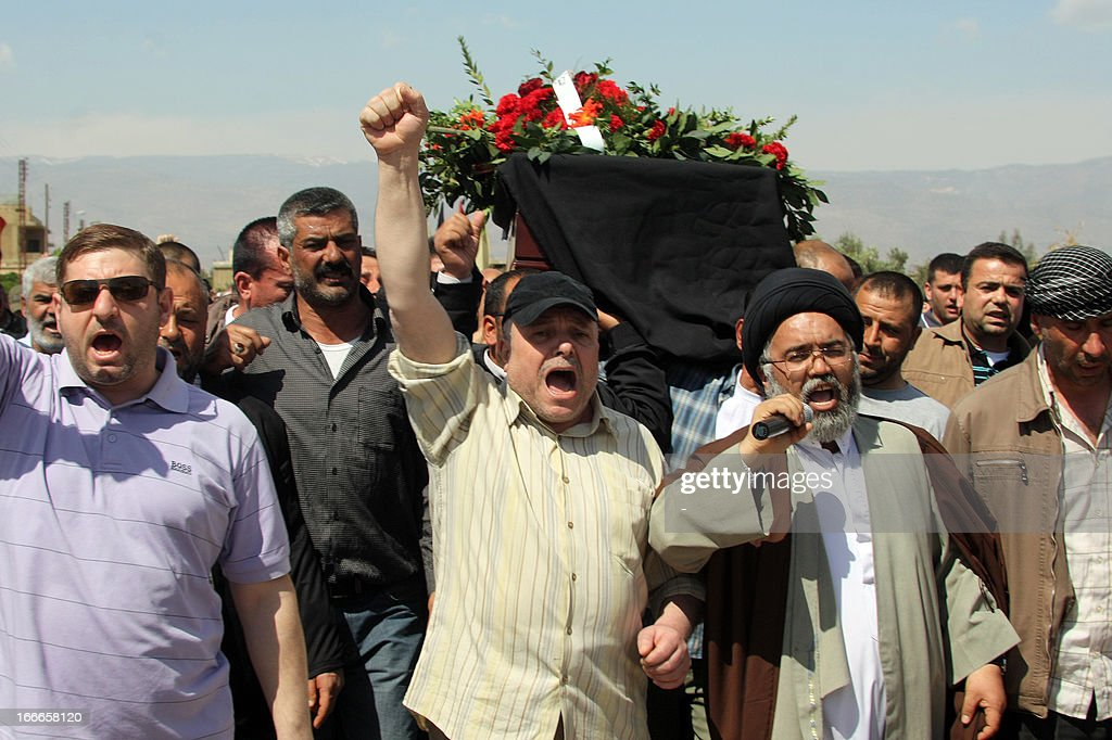 Mourners shout slogans as they carry the coffin of a 13-year old Lebanese child who was killed when the border town of Qasr, in the Hermel border region, came under artillery shell fire from Syrian territory, during his funeral procession in the village of Hosh Sayyed Ali, on the Syrian-Lebanese border, on April 14, 2013. Lebanese President Michel Sleiman issued a statement after the incident in Qasr, condemning the fire and adding that such spillover 'has only led to the deaths of innocent Lebanese who have nothing to do with the ongoing conflict taking place outside their country.' AFP PHOTO / STR