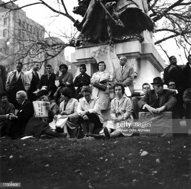 Mourners sit and stand by a statue near the White House after hearing of the assassination of President John F Kennedy on November 22 1963 in...