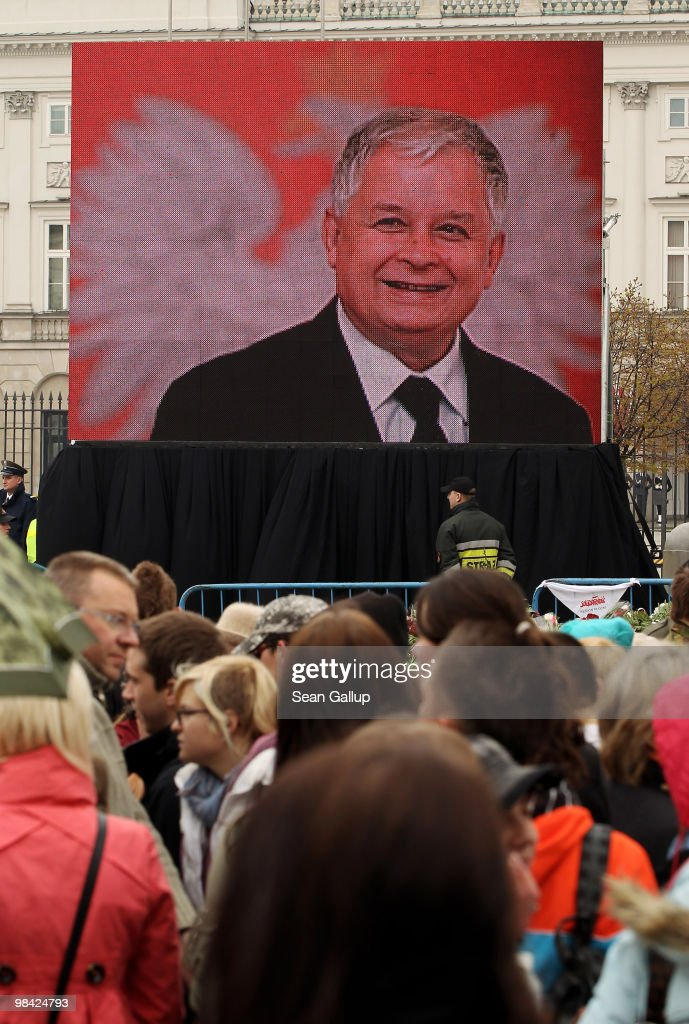 Mourners stand in front of a large screen television monitor presenting a slide show of late Polish President <a gi-track='captionPersonalityLinkClicked' href=/galleries/search?phrase=Lech+Kaczynski&family=editorial&specificpeople=544054 ng-click='$event.stopPropagation()'>Lech Kaczynski</a> outside the Presidential Palace on April 13, 2010 in Warsaw, Poland. Kaczynski, his wife Maria and leading members of the Polish military and government were killed when the presidential plane they were travelling in crashed while attempting to land at Smolensk, Russia, Saturday. The coffins of both Kaczynski and his wife are scheduled to be laid in state for public viewing today following the morning return of the coffin of Maria Kaczynska from Moscow.