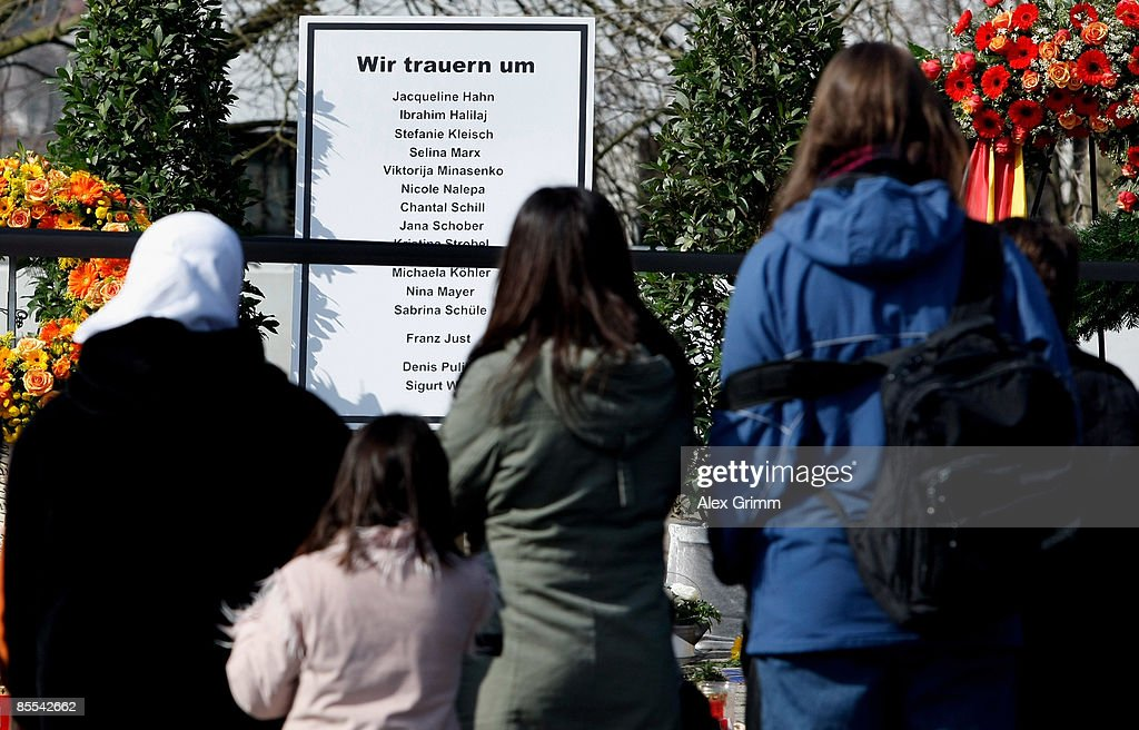 Mourners stand in front of a sign with the names of the victims outside Albertville high school on March 21, 2009 in Winnenden near Stuttgart, Germany. 17 year old Tim Kretschmer opened fire on Wednesday, March 11, 2009 on teachers and pupils at his former school, killing 15 people and leaving many more injured. Kretschmer fled the scene and shot himself dead after being cornered by police. German president Horst Koehler, German chancellor Angela Merkel and thousands of mourners held a memorial ceremony to commemorate the victims today.