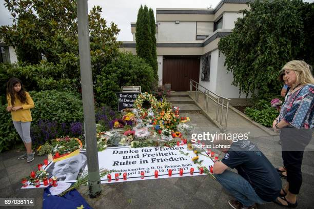 Mourners stand look to flowers candels and a portrait of Helmut Kohl in front of the home of former German Chancellor Helmut Kohl in Oggersheim...