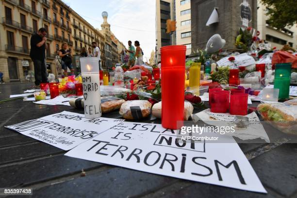 Mourners stand near flowers candles and tributes to the victims of the Barcelona attack on the Las Ramblas boulevard in Barcelona on August 19 two...