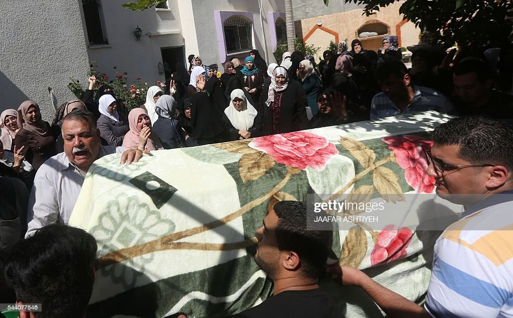 Mourners stand next to the body of Sondos al-Basha, a Palestinian woman who was killed in the Istanbul airport attack blamed on the Islamic State (IS) group on June 28, during her funeral in the West Bank town of Qalqilyah on July 1, 2016. The suicide attackers who launched the deadly Istanbul airport assault were planning to take dozens of passengers hostage, Turkish media reported on July 1, 2016, as CCTV of the bombers' faces emerged. Turkish officials have pointed blame at the Islamic State jihadist group for the gun and bomb spree at Ataturk airport, which left at least 44 people dead including 19 foreigners. / AFP / JAAFAR
