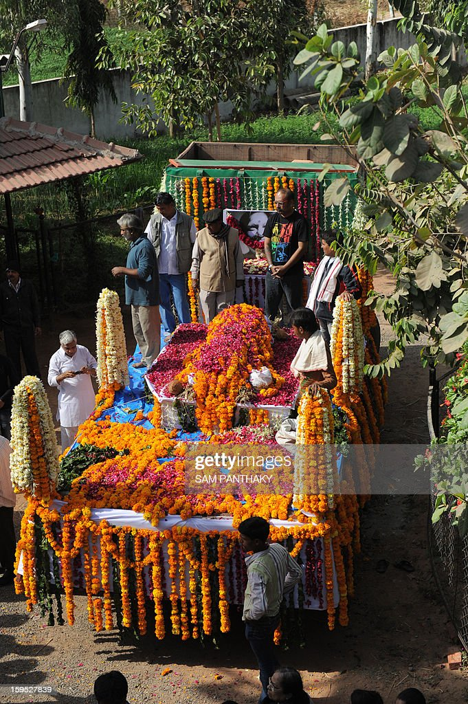 Mourners stand on a decorated vechile transporting the body of renowned sculptor, Jasuben Shilpi, 64, also known as the Bronze Woman of India at her residence cum workshop at Adalaj, some 25 kms from Ahmedabad on January 15, 2013. Shilpi passed away here last night following cardiac arrest. Shilpi's works like bronze standing figures of Mahatma Gandhi and Martin Luther King Jr are installed in Florida University, Jacksonville, Chicago and City of Charlotte, North Carolina. She had made more than 225 large size statues and 525 bust size statues in bronze. AFP PHOTO / Sam PANTHAKY