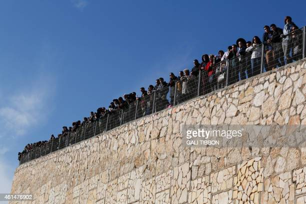 Mourners standing on a wall look on at a Jerusalem cemetery on January 13 during the funeral of four Jews killed in an Islamist attack on a kosher...